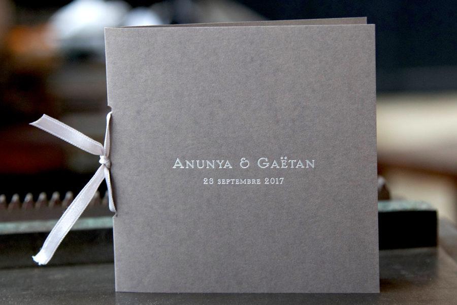 Cette photo représente un faire-part de mariage en livret sur papier grey relié par un ruban satin