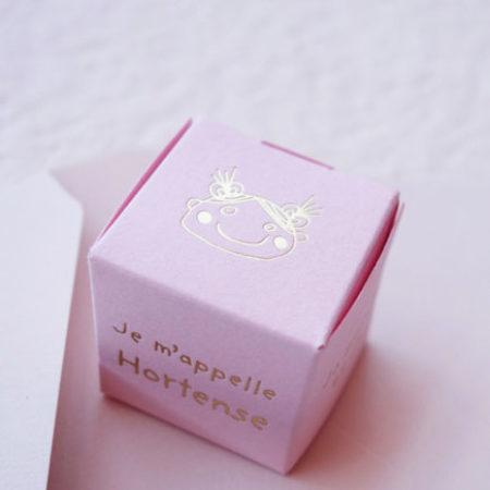 La photo représente le Faire-part naissance Cube avec la bouille de Lulu en gravure or sur une carte candy
